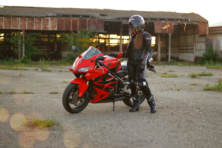 KRASNOYARSK, RUSSIA - June 23, 2018: Beautiful girl motorcyclist in full gear and helmet on a red and black Honda 2005 CBR 600 RR (PC37) Editorial
