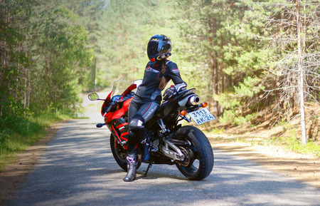 KRASNOYARSK, RUSSIA - June 23, 2018: Beautiful girl motorcyclist in full gear and helmet on a red and black Honda 2005 CBR 600 RR (PC37) Publikacyjne