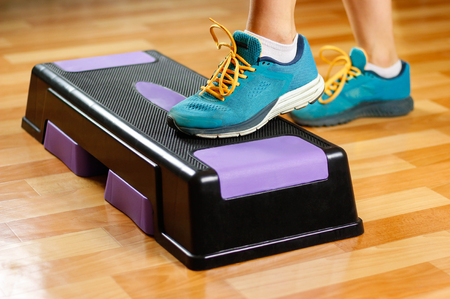 The girl in sneakers is engaged on the step-platform for fitness. Feet on the step for sports. Close up.