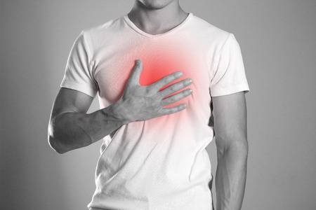 The man is holding his chest. Chest pain. Heartburn. The hearth is highlighted in red. Close up. Isolated background.
