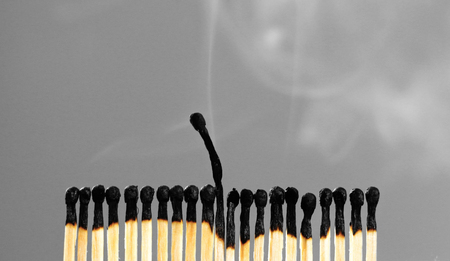 Extinct matches. Burning match among others on isolated background. Difference and uniqueness concept
