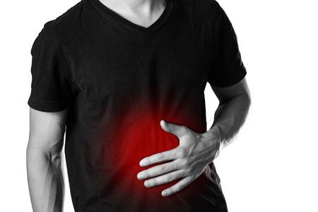 The man is holding his stomach. Abdominal pain. The hearth is highlighted in red. Close up. Isolated on white background.