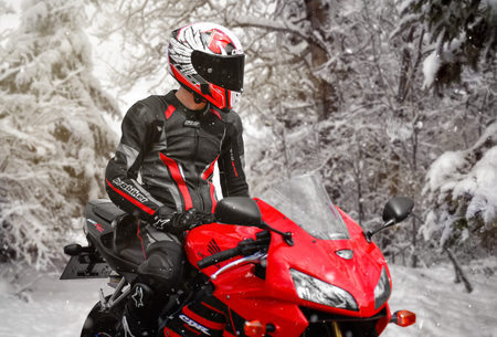 KRASNOYARSK, RUSSIA - July 17, 2018: Beautiful motorcyclist in full gear and helmet on a red and black Honda 2005 CBR 600 RR (PC37). In winter. Snow is falling