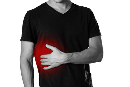The man is holding his side. Pain in the liver. Cirrhosis. The hearth is highlighted in red. Close up. Isolated on white background.