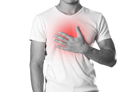 The man is holding his chest. Chest pain. Heartburn. The hearth is highlighted in red. Close up. Isolated on white background. Stock Photo