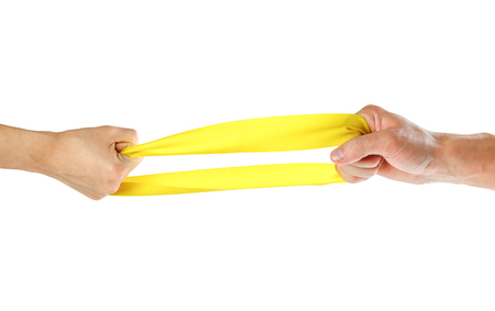The hands pull yellow athletic elastic band in different directions. Close up. Isolated on white background. Stockfoto