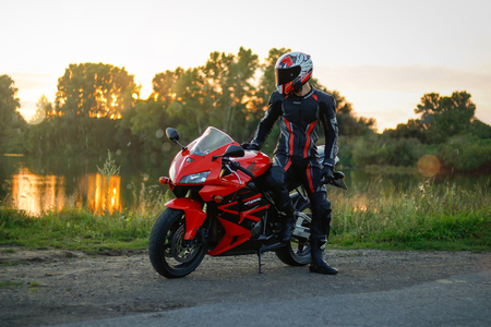 KRASNOYARSK, RUSSIA - August 23, 2018: Beautiful motorcyclist in full gear and helmet on a red and black Honda 2005 CBR 600 RR (PC37)