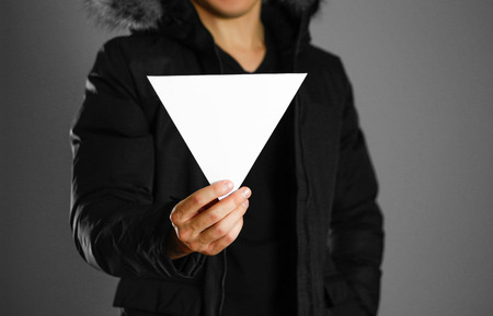 A man in a warm winter jacket holds a triangular white leaflet. Blank paper. Close up. Isolated background.