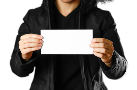 A man in a warm winter jacket holding a white leaflet. Blank paper. Close up. Isolated on white background.