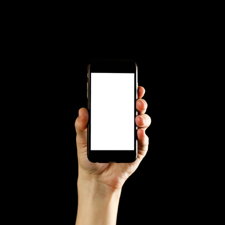 Hand holding black smartphone with blank white screen. Close up. Isolated on black background. Stock fotó