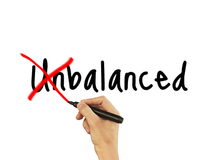 Unbalanced - male hand writing text on white background.