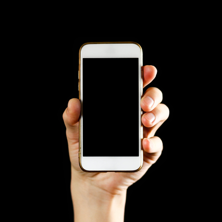 Hand holding white smartphone with blank black screen. Close up. Isolated on black background.