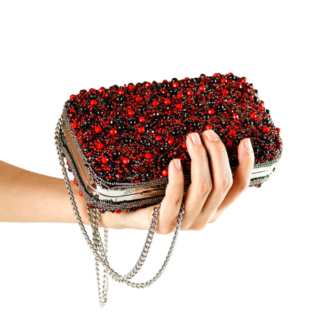 Hand holds a small red female purse covered with stones. Clutch. Close up. Isolated on white background Stock Photo