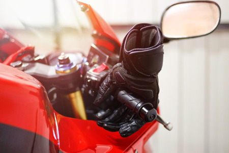 Black leather motorcycle gloves is lying on a red sports bike