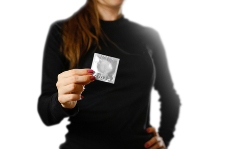 Girl's hand holding a single condom. Close up. Isolated on white background.