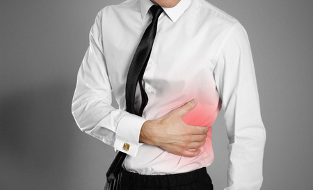 Uomo d'affari in camicia bianca e cravatta che gli tiene il fianco. Dolore al fegato. Fegato di Syros. Sfondo isolato.