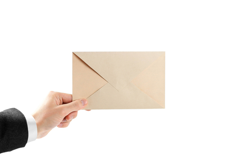 The hand in white shirt and black jacket holding the envelope. Close up. Isolated on white background.