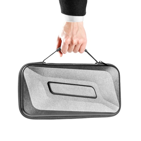 A mans hand in white shirt and black jacket holds a black plastic suitcase. Close up. Isolated on white background. Stock Photo
