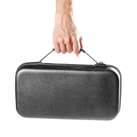 A mans hand holds a black plastic suitcase. Close up. Isolated on white background.
