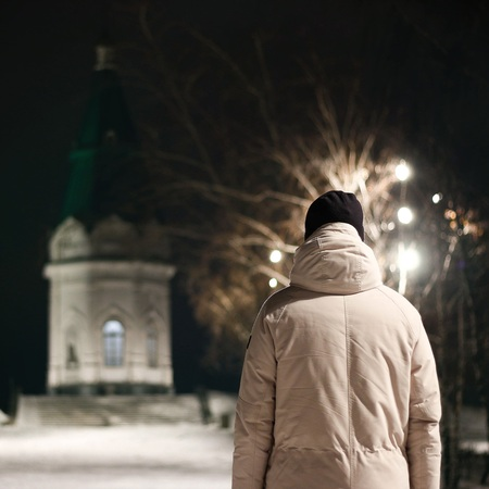 A man looks at the chapel. A man stands facing the Church.