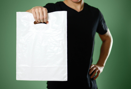 A man holding a white plastic bag. Close up. Isolated on green background.