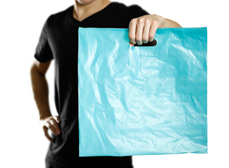 A man holding a turquoise plastic bag. Close up. Isolated on white background. Stock Photo