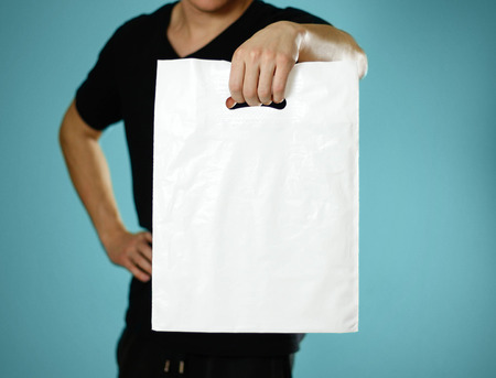 A man holding a white plastic bag. Close up. Isolated on blue background. Stock Photo