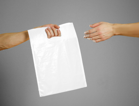 A mans hand passes a white plastic bag. Close up. Isolated on grey background. Stock Photo