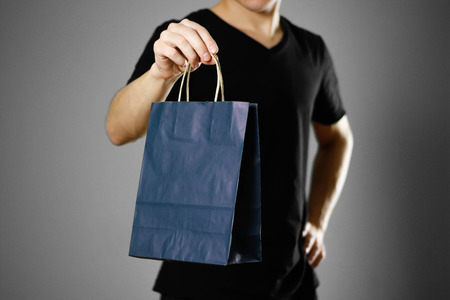 Man holding a gift bag. Close up. Isolated on grey background.
