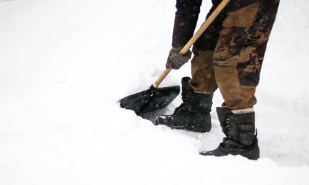 A man cleans snow with a shovel. The dusting of snow. Close up.