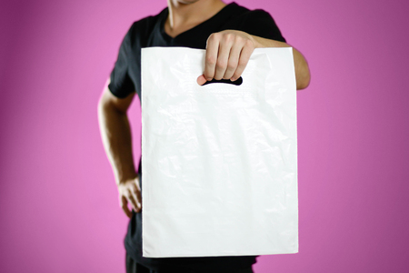 A man holding a white plastic bag. Close up. Isolated on pink background.
