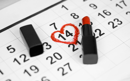 Valentines day and Holidays concept. Calendar sheet with 14th february date marked by red heart shape with red lipstick. Close up. Stock Photo