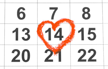 Valentines day and Holidays concept - Calendar sheet with 14th february date marked by red heart shape. Close up. Stock Photo