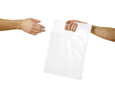 A mans hand passes a white plastic bag. Close up. Isolated on white background.