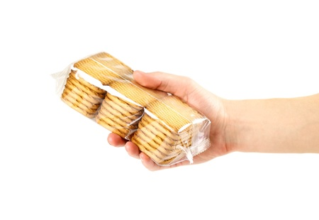 Hand holding a Golden cookie in a transparent package. Close up. Isolated on white background.