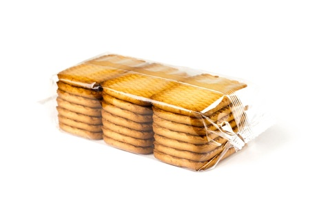 Golden cookies in a transparent package. Close up. Isolated on white background.