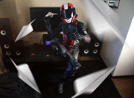Beautiful motorcyclist in full gear and helmet launches paper airplane. Stock Photo