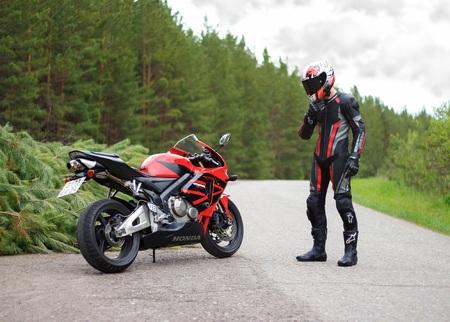 KRASNOYARSK, RUSSIA - March 24, 2018: Beautiful motorcyclist in full gear and helmet on a red and black Honda 2005 CBR 600 RR (PC37).
