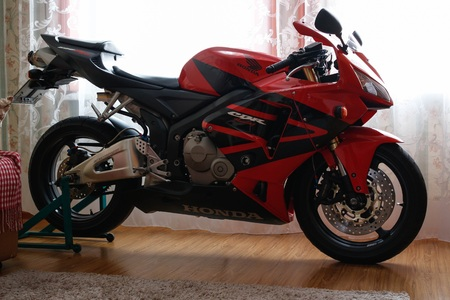 KRASNOYARSK, RUSSIA - March 6, 2019: Red and black sportbike Honda CBR 600 RR 2005 PC37 in house. The motorcycle in the apartment. Winter storage. 報道画像