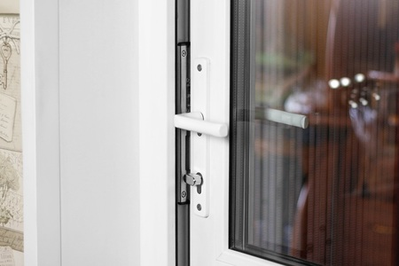 A mans hand opens a white plastic door. Close up.