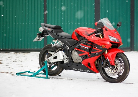 KRASNOYARSK, RUSSIA - March 18, 2019: Red and black sportbike Honda CBR 600 RR 2005 PC37 in winter. The bike is on the snow.