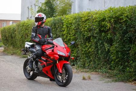 KRASNOYARSK, RUSSIA - May 29, 2018: Beautiful motorcyclist in full gear and helmet on a red and black Honda 2005 CBR 600 RR (PC37).