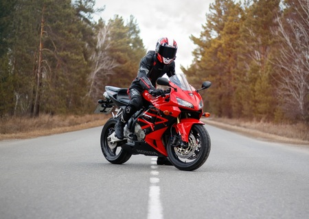 KRASNOYARSK, RUSSIA - March 24, 2019: Beautiful motorcyclist in full gear and helmet on a red and black Honda 2005 CBR 600 RR (PC37).