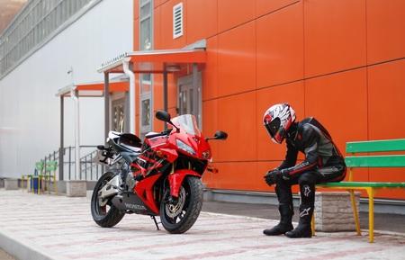 KRASNOYARSK, RUSSIA - April 3, 2019: Beautiful motorcyclist in full gear and helmet on a red and black Honda 2005 CBR 600 RR (PC37). 報道画像