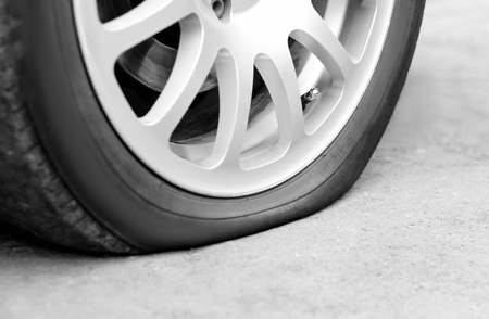 Flat tire on the car. Silver forged wheel. Close up.