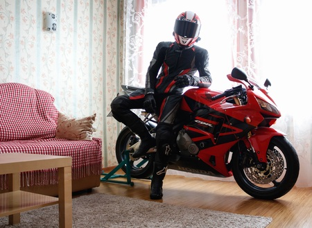 KRASNOYARSK, RUSSIA - December 21, 2018: Beautiful motorcyclist in full gear and helmet on a red and black Honda 2005 CBR 600 RR (PC37) in house.