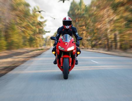 KRASNOYARSK, RUSSIA - April 23, 2019: Beautiful motorcyclist in full gear and helmet on a red and black Honda 2005 CBR 600 RR (PC37).