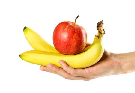 Mano che tiene le banane e la mela rossa. Avvicinamento. Isolato su sfondo bianco.
