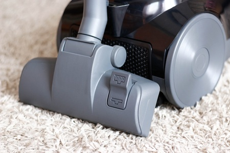 A beautiful black vacuum cleaner stands on a beige carpet with a long pile. Close up.