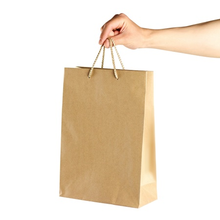 Hand holding a paper bag. Close up. Isolated on white background. 写真素材